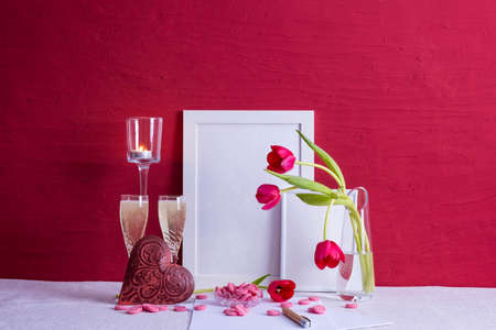 two glasses with champagne, writing materials, tulips in a vase, iron heart, photo frames on a red background on the table Zdjęcie Seryjne