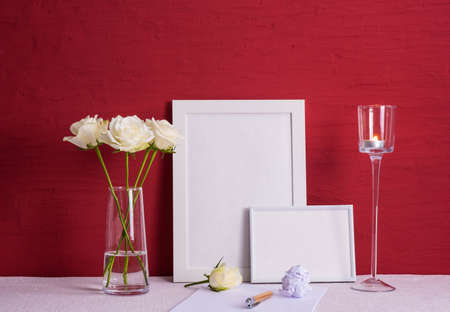 burning candle, writing materials, white roses in a glass vase, white photo frames on a red background on the table Stock fotó