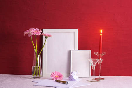 burning candle, writing materials, pink gerberas in a vase, photo frames on a red background on the table
