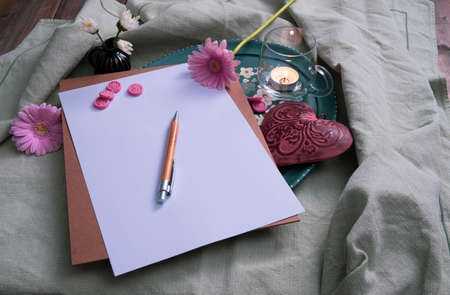 metal heart and gerbera, writing materials on the table, near a candle and decorations on a green background