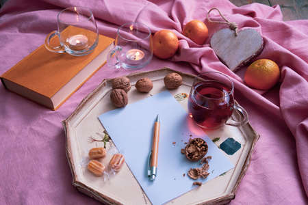 tea drink, writing materials on the table, fruits and nuts, near a candle and decorations on a pink background Zdjęcie Seryjne