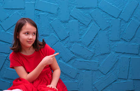 girl in a red dress sits on the floor and shows a finger to the side, on a blue background Reklamní fotografie