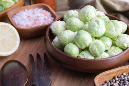 peeled and washed Brussels sprouts lie in a wooden bowl, next to salt and spices, on the table Stok Fotoğraf