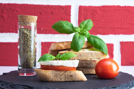 basil, white bread croutons with mozzarella, spices and tomato on a stone stand on a brick background