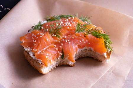 baked bun oiled with fresh cream, garnished with smoked fish trout and sprinkled with fresh dill and sesame seeds, delicious and fresh on a black background