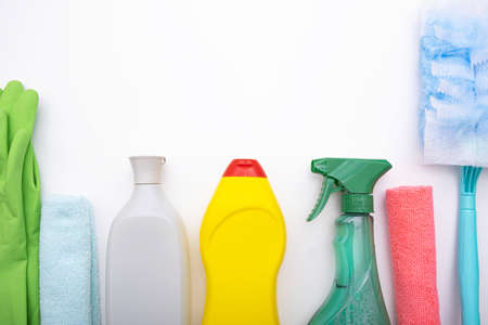 on a white background colored brushes, rags, liquids and gloves for cleaning the house, close-up Imagens