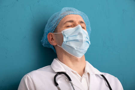 tired nurse leaned against the wall and closed his eyes, blue background Banque d'images