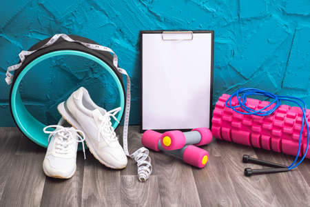 workout at home - white sneakers, dumbbells, jump rope, measurement tape, note board and massage roller, close-up and blue background
