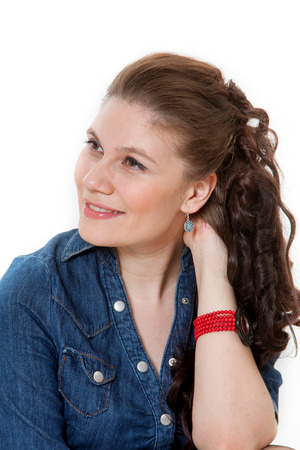 The girl sits in a jeans dress on a white background. photo