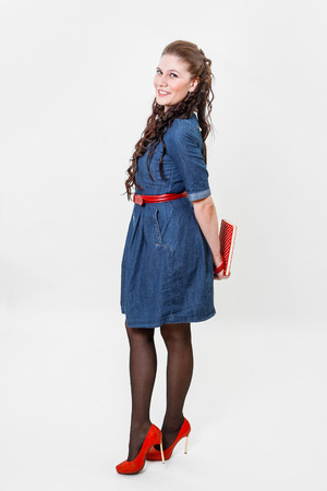 allocated on white: The girl with long black hair, in a blue jeans dress and red shoes on a white background
