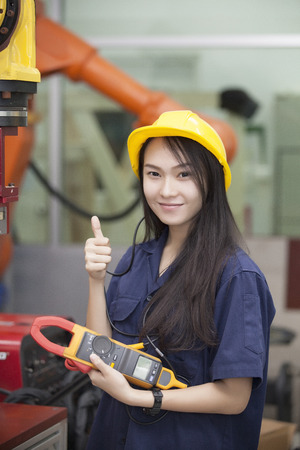 production engineer: Manufacturing worker operating a robot machine  Stock Photo