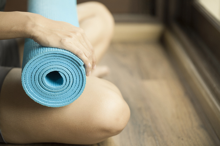 yoga: Young woman holding a yoga mat