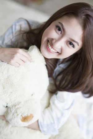 Portrait of pretty young woman with teddy bear photo