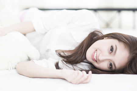 woman portrait: Young woman smile face close up while lying on the bed
