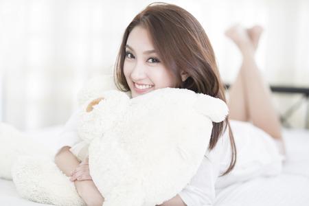 ベッドの上に横たわっている間若い女性の笑顔の顔クローズ アップ 写真素材