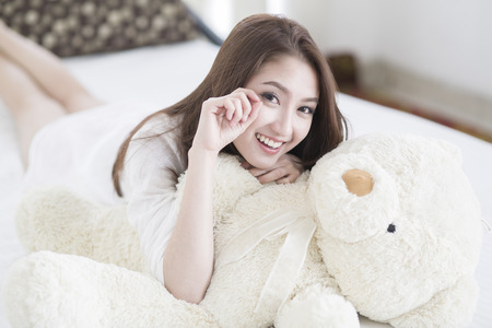 niña: Cara de la sonrisa de la mujer joven de cerca mientras está acostado en la cama