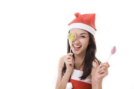 santa suit: happy smile girl wearing a santa suit holding a candy for christmas on white background