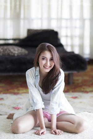 Beautiful asian woman smiling happily sitting among morning sunshine