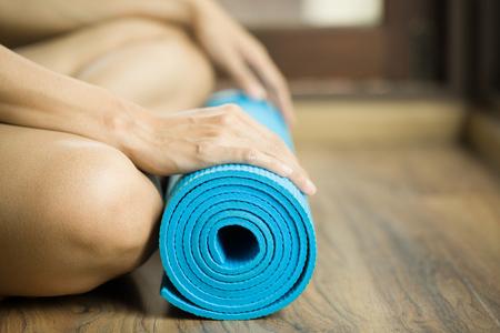 pesas: Mujer joven que sostiene una estera de yoga Foto de archivo