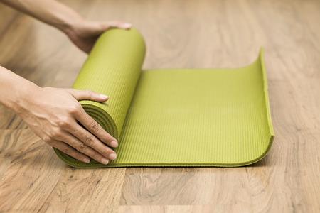 Young woman holding a yoga mat Standard-Bild