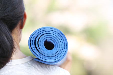 salud y deporte: Mujer joven que sostiene una estera de yoga Foto de archivo