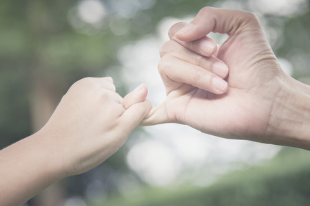 promising: A mother and her child hooking their fingers to make a promise, vintage style