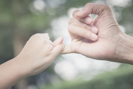 Una madre y su hijo enganchando sus dedos para hacer una promesa, estilo vintage Foto de archivo