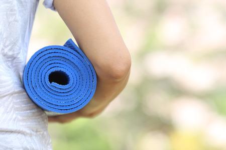 Young woman holding a yoga mat in sakura garden