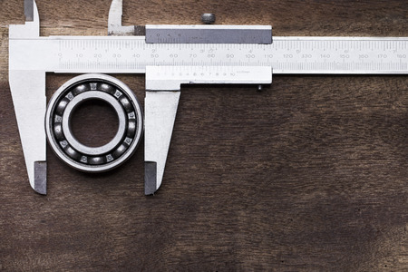 chromium plated: ball bearing and vernier on wooden background