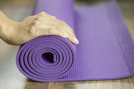 Young woman holding a yoga mat 스톡 콘텐츠