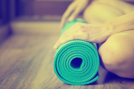 classes: Young woman holding a yoga mat Stock Photo