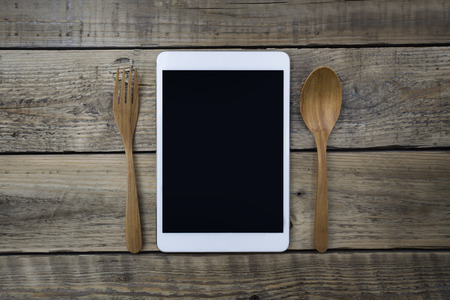 cell phone addiction: Mobile smart tablet served on wood plate