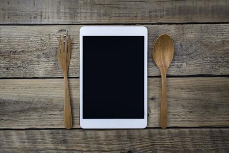 food technology: Mobile smart tablet served on wood plate