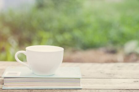 Coffee cup and book on wooden table photo
