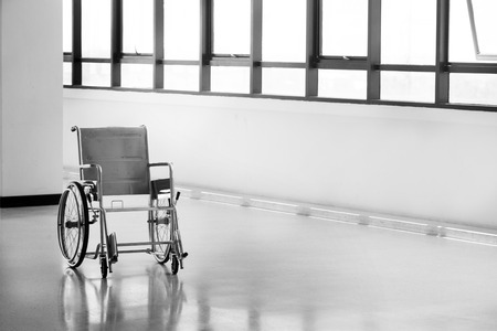 mobility nursing: Empty wheelchair parked in hospital hallway