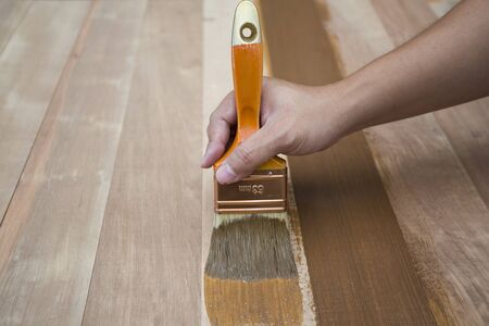 treated board: Applying protective varnish on a wooden furniture