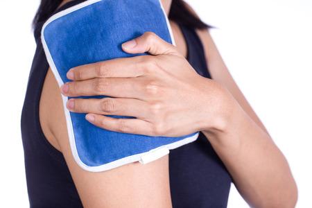 musculos: mujer que pone una bolsa de hielo sobre su dolor en el hombro Foto de archivo