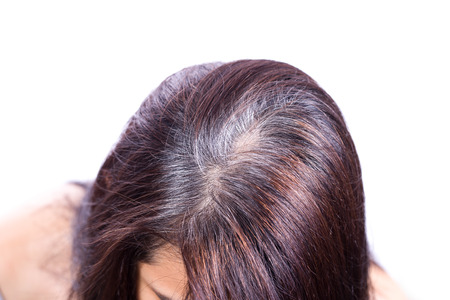 gray: Young woman shows her gray hair roots
