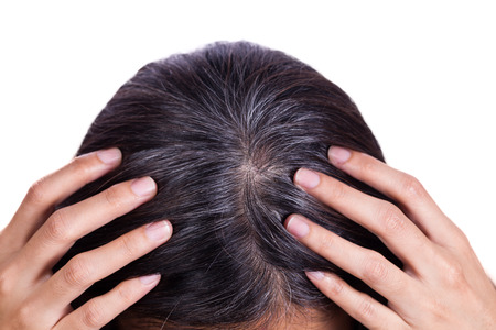 gray hairs: Young woman shows her gray hair roots