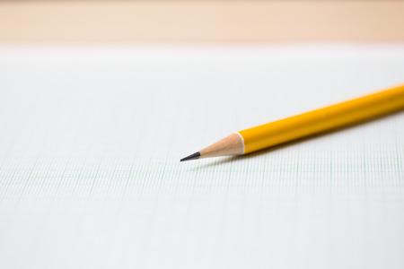 lapiz y papel: primer plano de un lápiz de color amarillo en el gráfico de fondo de papel