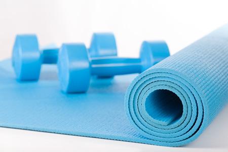 Yoga mat and dumbbells on white background