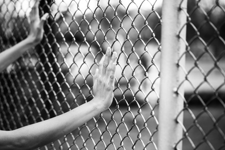 Hand holding on chain link fence, black and white concept photo