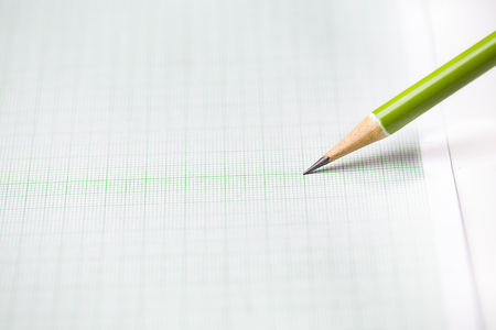secretarial: close-up green pencil on graph paper background