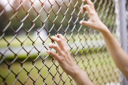 chain link fence: Hands holding on chain link fence