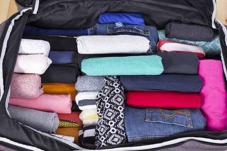 open suitcase: Open suitcase with clothing in the room