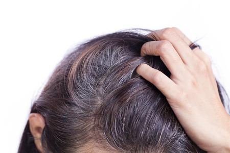 De jonge vrouw toont haar grijze haarwortels