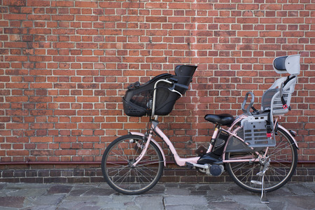 child seat: Bicycle child seat is attached with brick background Stock Photo