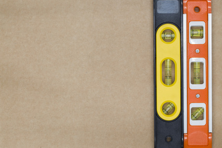 leveler: red and yellow building level on the brown paper background