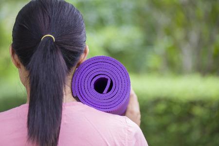 yoga mat: Young woman holding a yoga mat Stock Photo