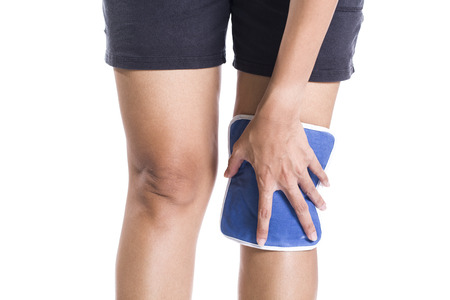 physical therapy: woman applying cold pack on swollen hurting knee